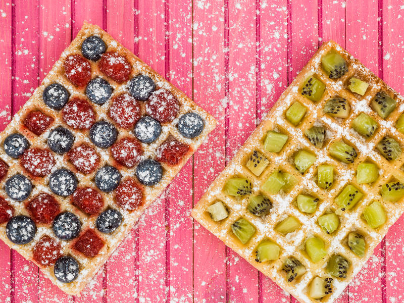 Fruit Waffles with Raspberries Blueberries and Kiwi Fruit and Icing Sugar stock photo
