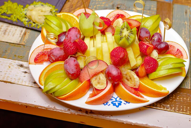 Fruit on a white plate. Sliced fruit on a colorful table stock image