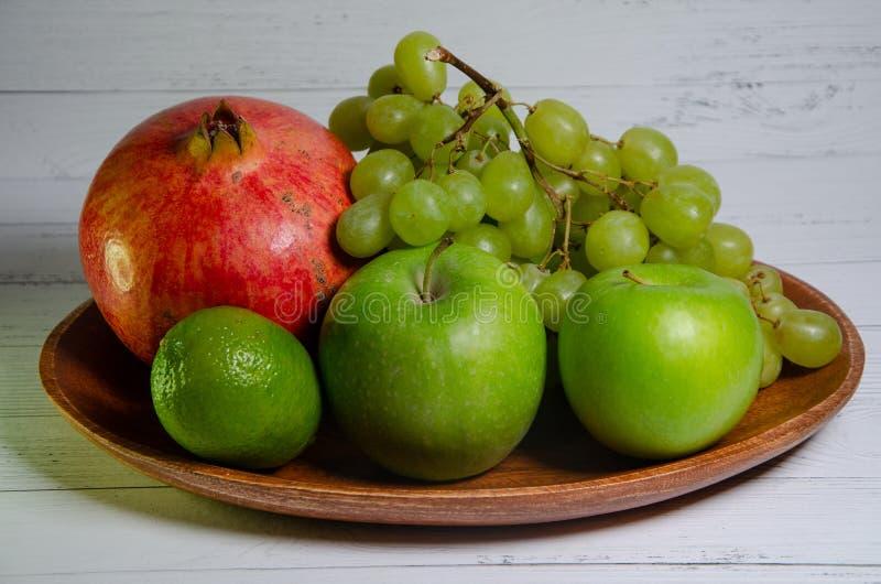 Fruit on a wooden bowl stock photos