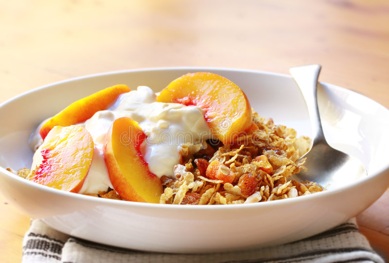 Fruit Yoghurt and Muesli. Bowl of muesli topped with yoghurt and fresh nectarine slices. A delicious, healthy breakfast royalty free stock photos