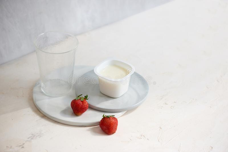 Fruit yogurt in plastic container with one strawberry on white background.  royalty free stock image