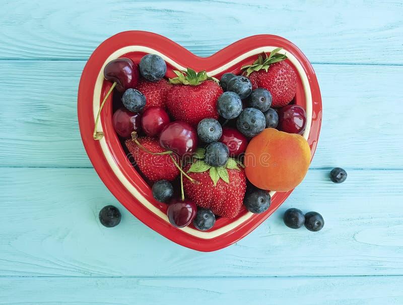 fruitaardbei, bosbes, kers, de plaathart van abrikozen anti-oxyderend detox op blauwe houten stock foto
