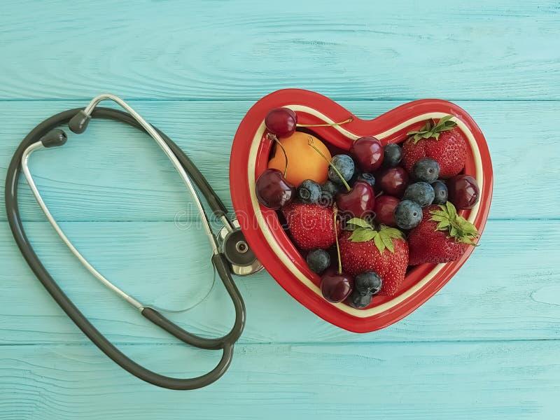 Fruitaardbei, bosbes, kers, het ideehart van de abrikozenplaat op blauw houten gemengd stethoscoop zoet middel tegen oxidatie royalty-vrije stock foto