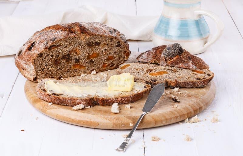 Fruitbrood met boter op witte houten achtergrond stock foto