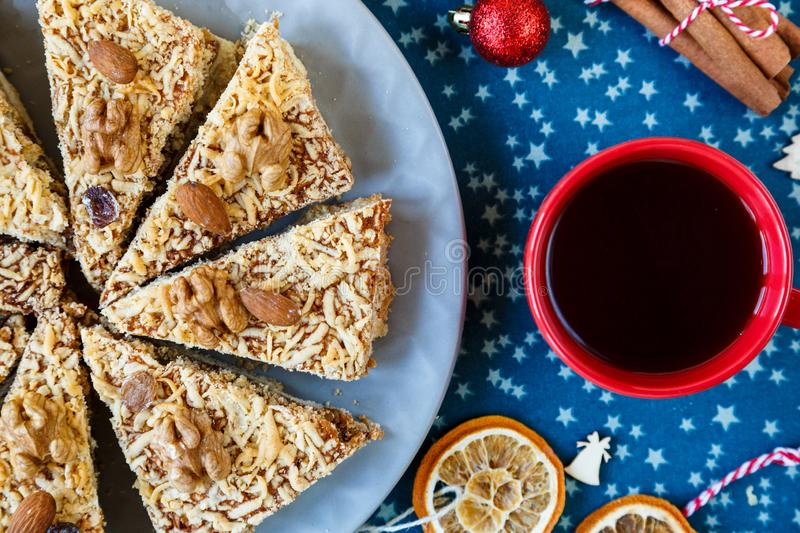 Fruitcake, decor, branches of spruce, plate with a cake and red cup of coffee or tea on the blue placemat. New year and Christmas stock photo
