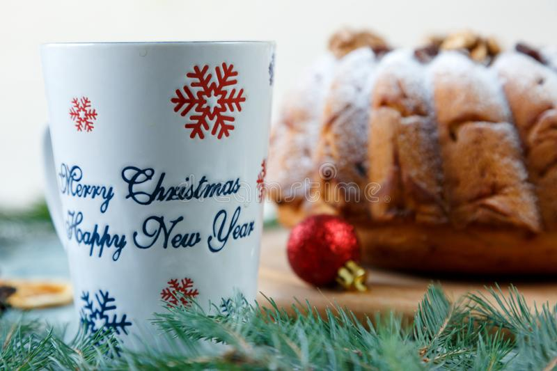 Fruitcake, decor, branches of spruce, plate with a cake and red cup of coffee or tea on the blue placemat. New year and Christmas royalty free stock image