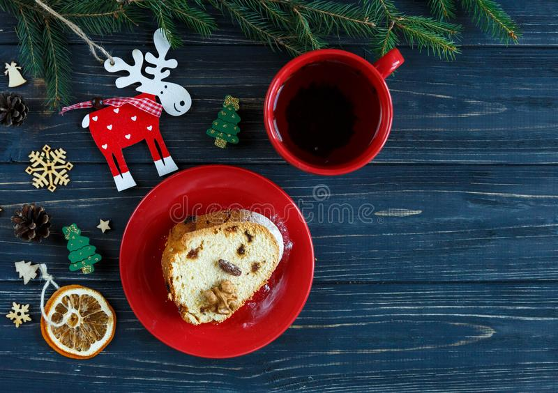 Fruitcake, decor, branches of spruce, plate with a cake and red cup of coffee or tea on the gray wooden table. New year stock image