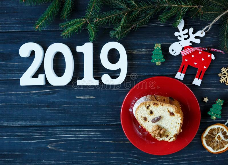 Fruitcake, decor, branches of spruce, plate with a cake and red cup of coffee or tea on the gray wooden table. New year stock photography