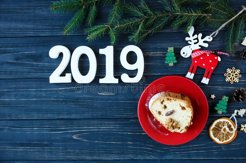 Fruitcake, decor, branches of spruce, plate with a cake and red cup of coffee or tea on the gray wooden table. New year stock photos