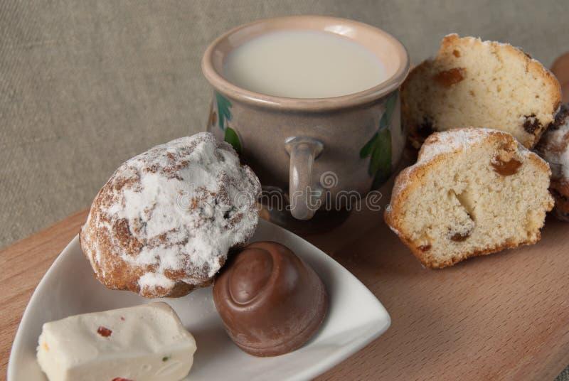 Fruitcakes, doces, uma caneca com leite imagem de stock royalty free