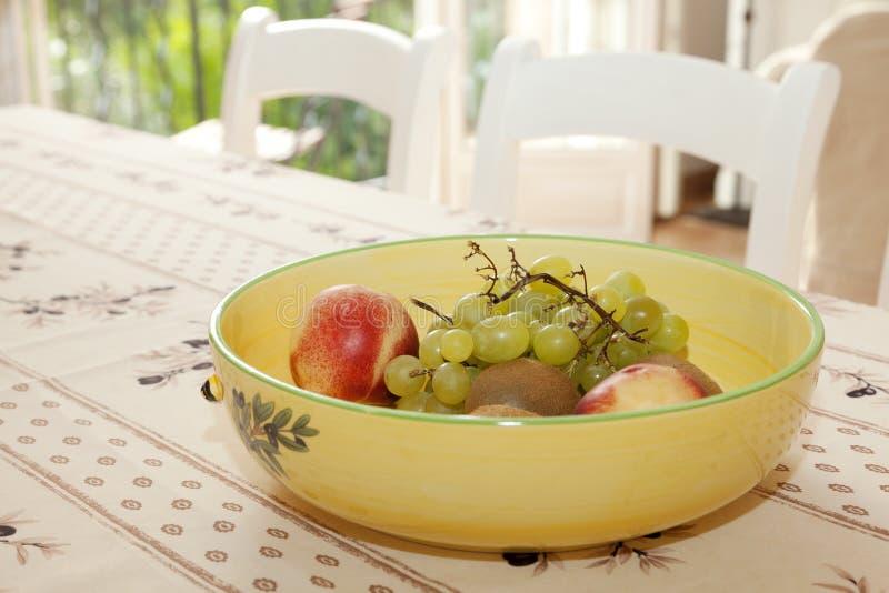 Fruitkom op een lijst stock afbeeldingen