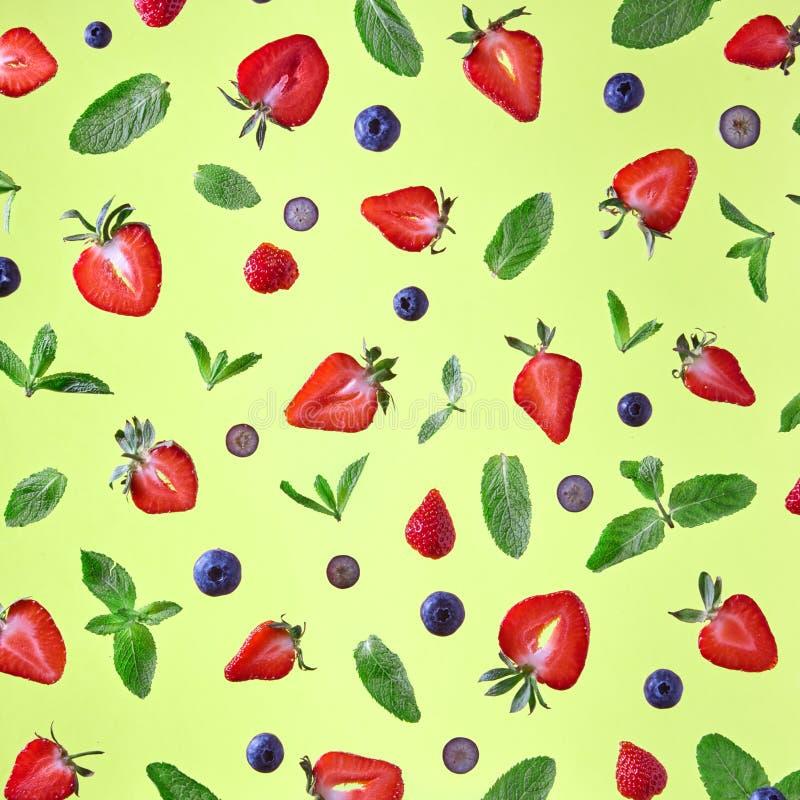Fruitpatroon van verse bessen en groene bladeren op gele achtergrond wordt gemaakt die royalty-vrije stock fotografie