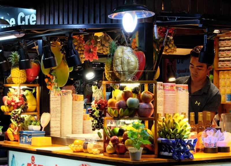 Fruitroomijs en cocktailkiosk, jonge Aziatische mannelijke verkoper, fruitwinkel stock foto