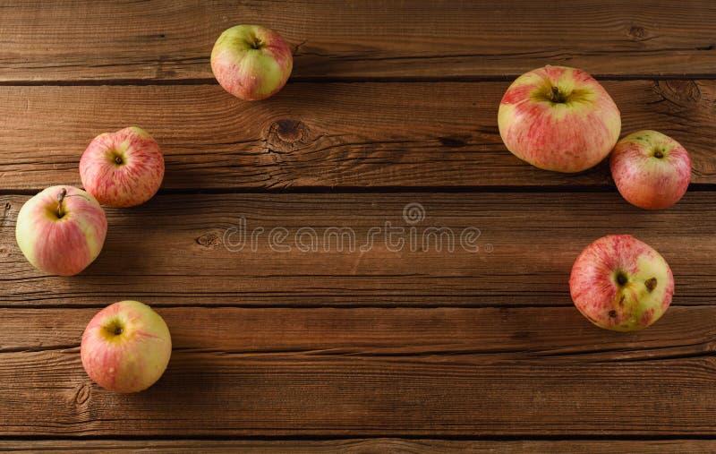 fruits органическо Вкусные неидеальные яблоки на старой деревянной предпосылке стоковое изображение