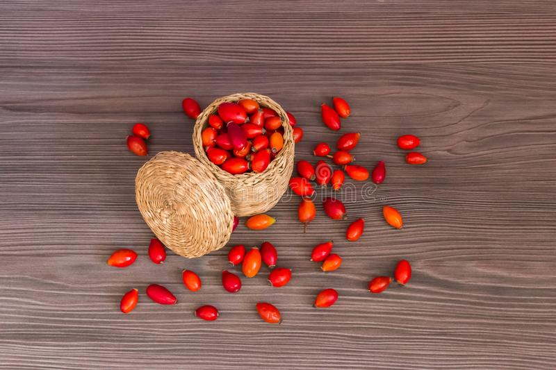 Fruits of autumn. Rose hips in a basket on a wooden surface , healthy food from nature. Concept of autumn background stock image