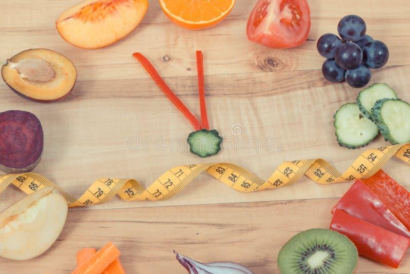 Fruits avec des légumes dans la forme de l'horloge et du ruban métrique Temps à la nutrition saine image stock