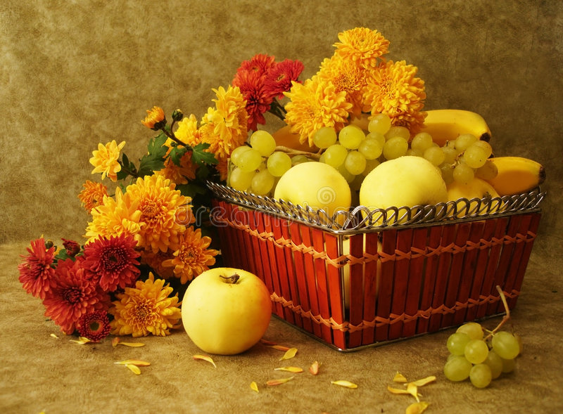 Fruits on basket and flowers royalty free stock images