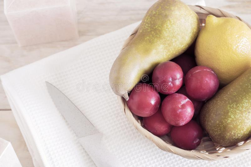 Fruits in the basket on the table, pears and lemons, along with the plums of the servers, royalty free stock photo