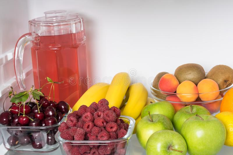 Fruits, berries and a drink lie inside a white open refrigerator, close-up stock image