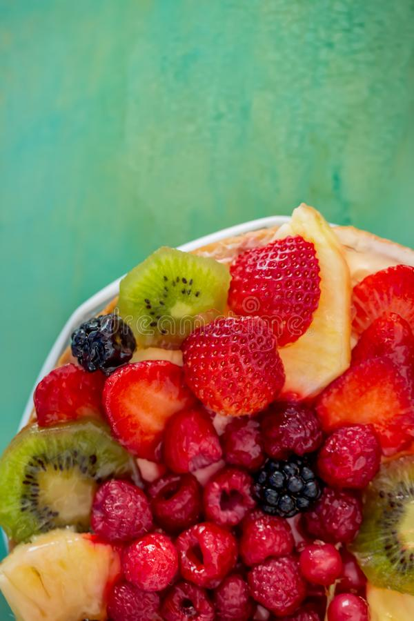 Fruits and berries in sweet gelatin on the cake. Background of strawberries, kiwi, currants, raspberry, pineapple, blackberry. royalty free stock photos