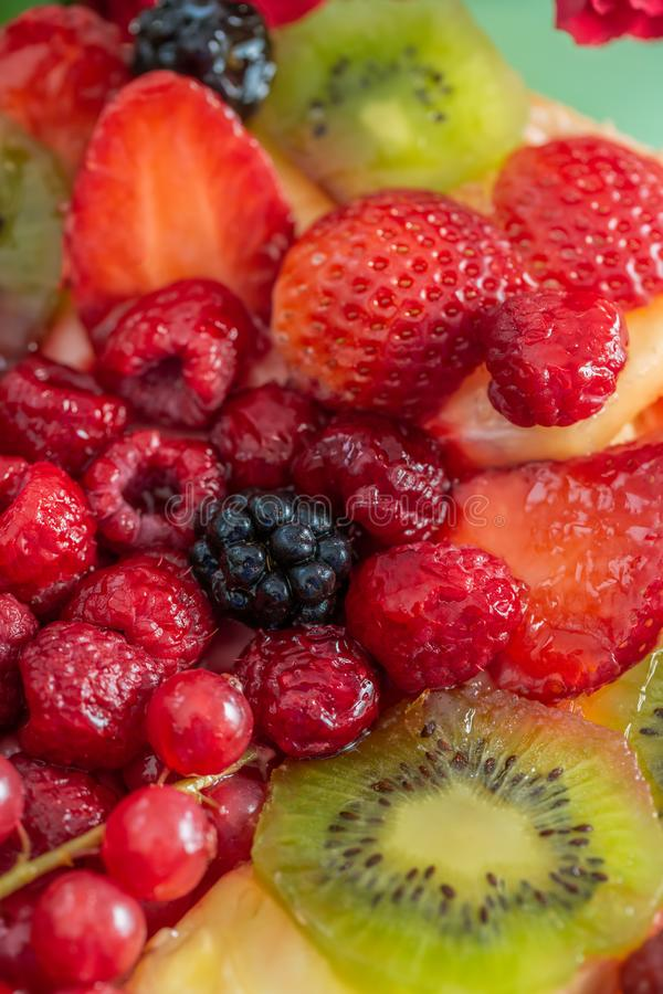 Berries in sweet gelatin on the cake. Background of strawberries, kiwi, currants, raspberry, pineapple, blackberry. Delicious dess stock photography