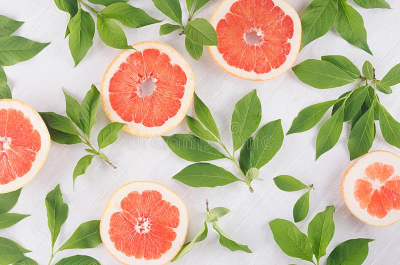 Fruits colorful fresh background - slice grapefruit and green leaves on white wood board. Fruits colorful fresh background - slice grapefruit and green leaves stock image
