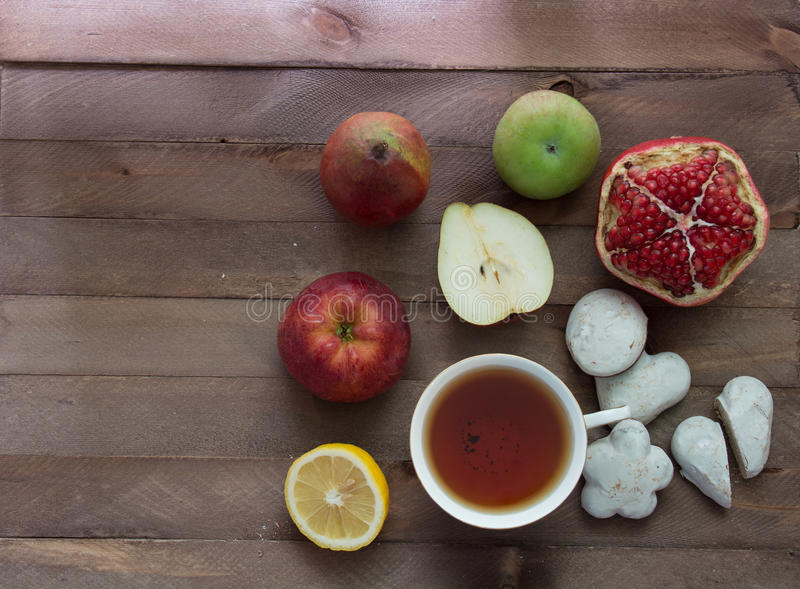 Fruits, cookies and a cup of tea on a wooden table royalty free stock image