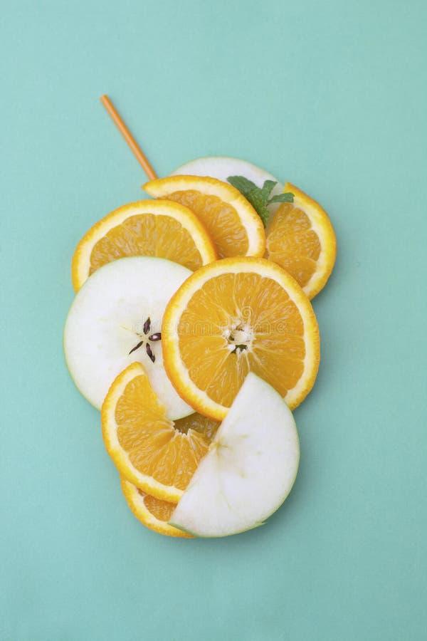 Fruits coup?s en tranches oranges d'orange et de pomme, jus d'orange avec la paille de cockail sur le fond bleu Vue sup?rieure image stock