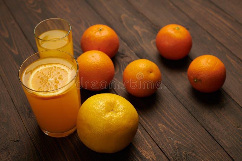 Fruits d'orange frais entiers et tranchés sur fond de bois foncé - aliments naturels et sains Verre de cocktail de fruits image stock