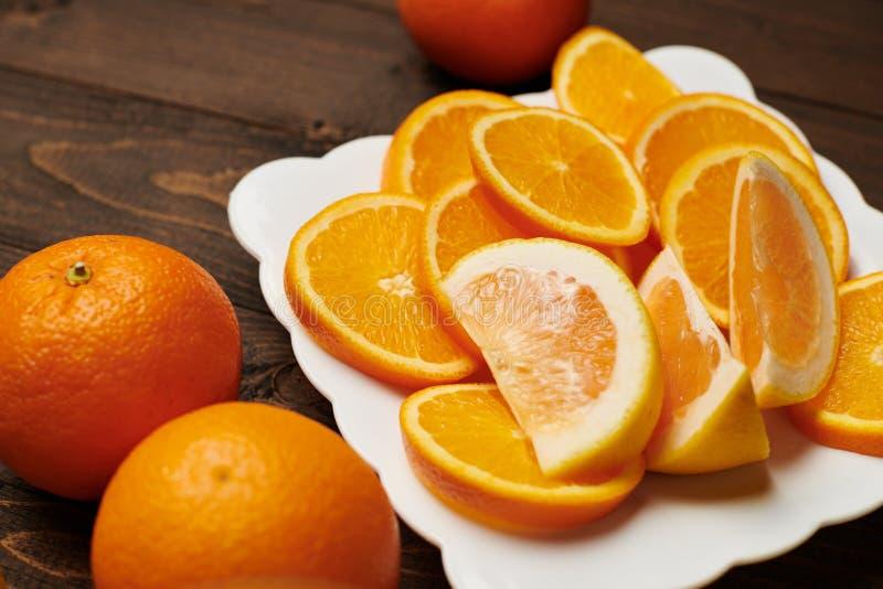 Fruits d'orange frais entiers et tranchés sur une assiette, fond en bois foncé - nourriture naturelle et saine images libres de droits