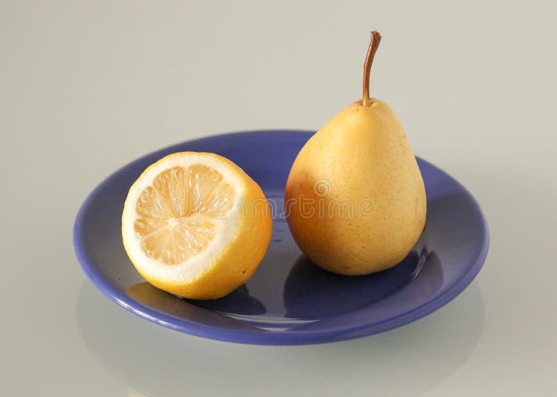 Fruits d'un plat bleu sur un fond gris photos libres de droits