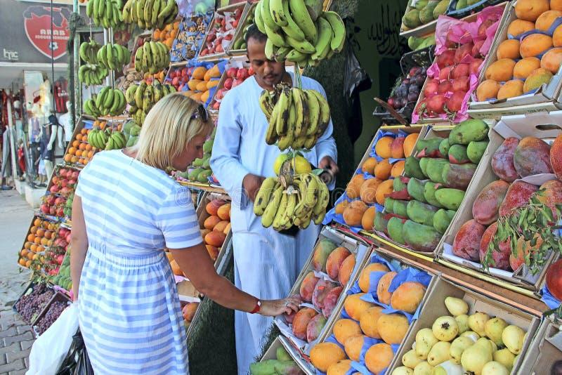 Fruits de achat de touristes de femme au marchand ambulant mangues, grenades, goyave photos stock