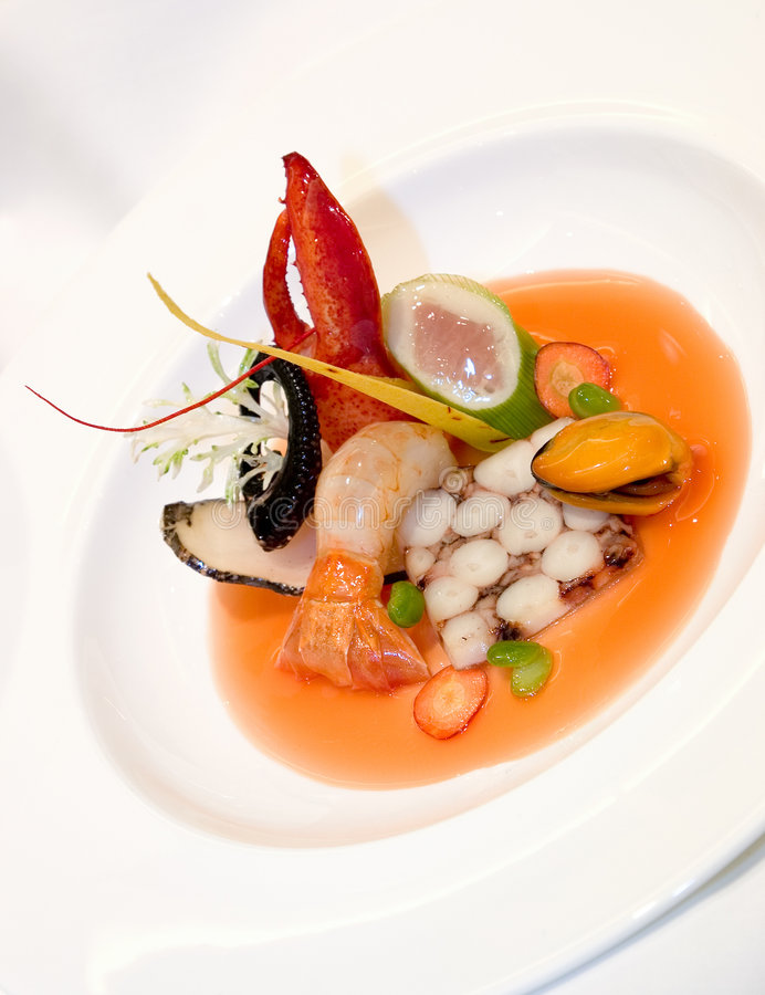 Fruits de Mer. Octopus Terrine, poached scallop mousse, with tuna belly, steamed butter mussels, langoustine and tomato lobster fume royalty free stock image