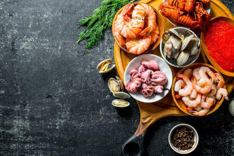 Fruits de mer Crevette, écrevisses, huîtres, poulpe et caviar dans des cuvettes sur la planche à découper image libre de droits