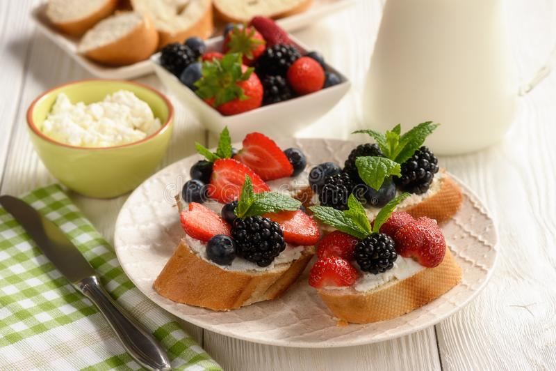 Fruits de petit déjeuner et sandwichs sains à ricotta avec des fraises, des myrtilles et des mûres photo libre de droits