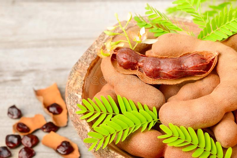 Fruits de tamarinier et feuilles fraîches sur le conseil en bois photo stock
