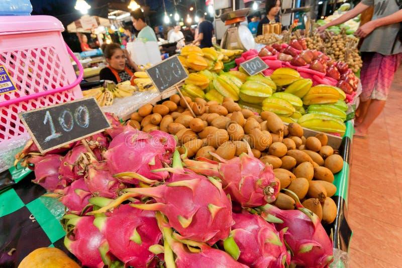 Fruits du dragon de achat de personnes et légumes tropicaux sur le marché en plein air avec le grand choix de la nourriture savou photo stock