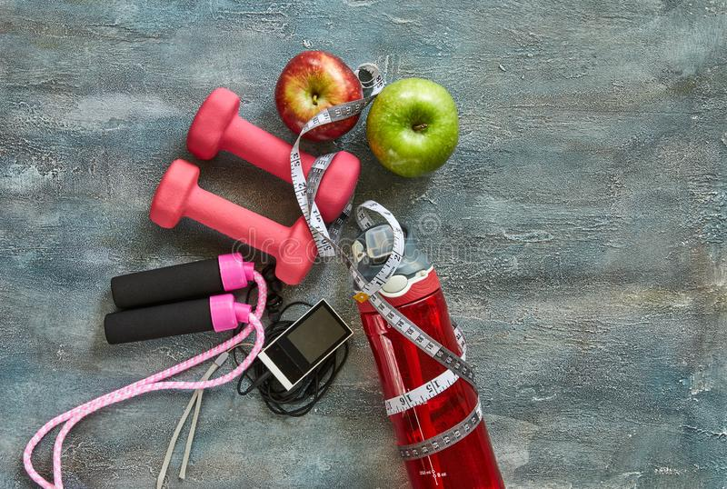 Fruits, dumbbells, a bottle of water, rope, meter, player on a blue background with stains royalty free stock image