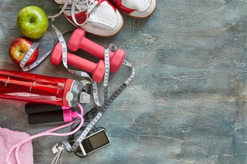 Fruits, dumbbells, a bottle of water, rope, sneakers and a meter on a blue with divorce background stock image