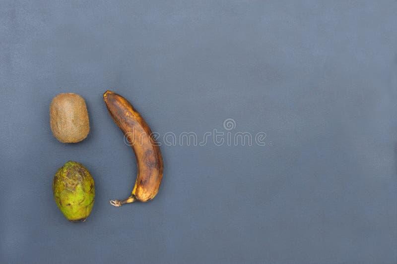 Fruits et avocat putréfiés et vieux sur le fond gris images stock