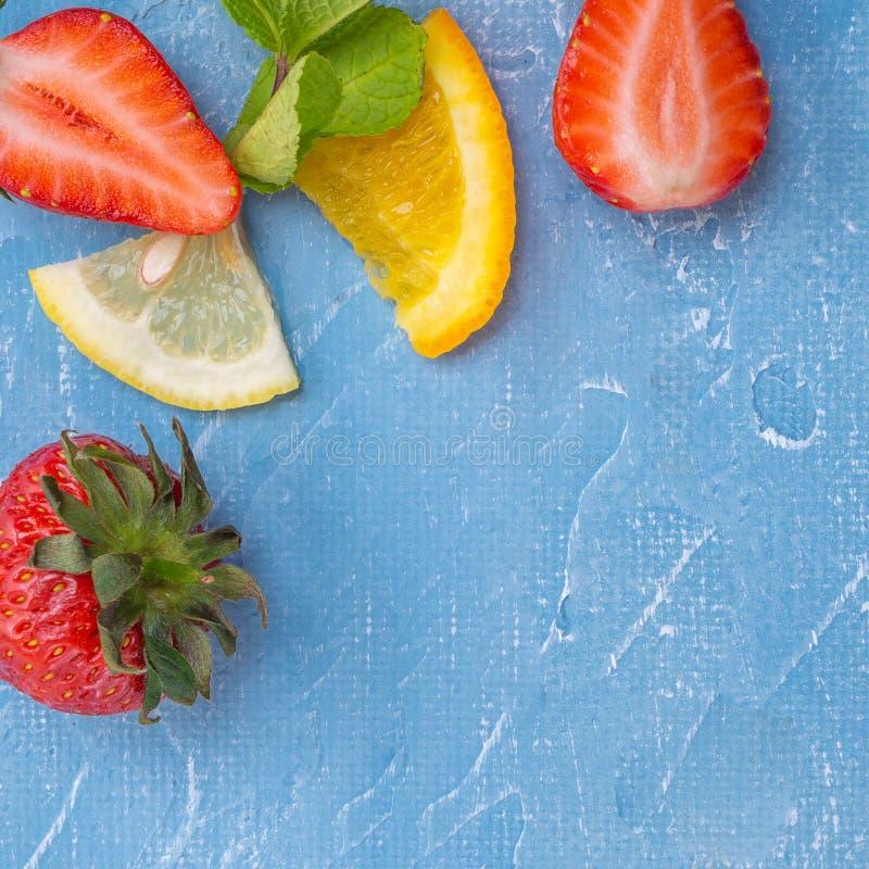 Fruits et baies mélangés - fraises, oranges, citrons et feuilles de menthe photos stock