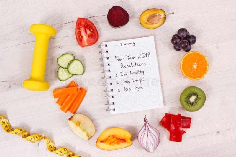 Fruits et légumes naturels, haltère avec le ruban métrique et résolutions de nouvelle année écrites en bloc-notes images libres de droits