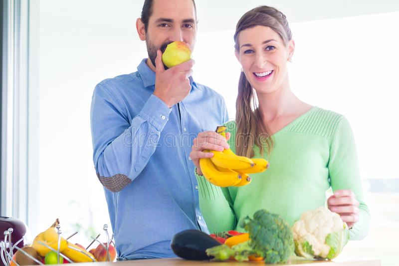 Fruits et légumes sains vivants de consommation de couples photo stock