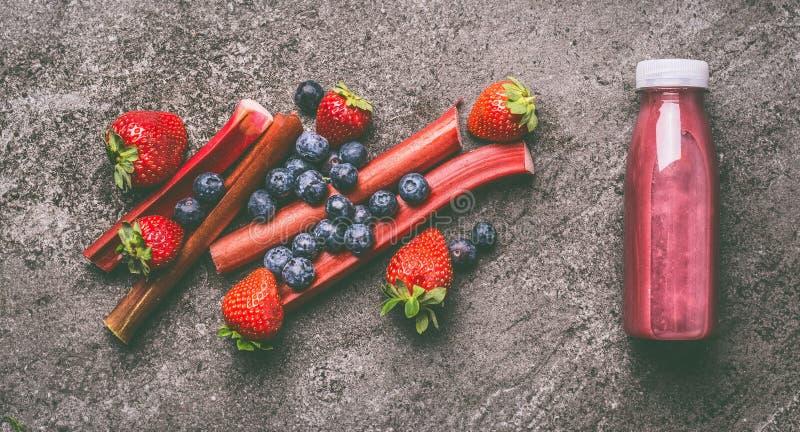 Fruits et smoothie organiques rouges de baies avec la rhubarbe, les myrtilles et les fraises dans la bouteille sur la table grise image stock