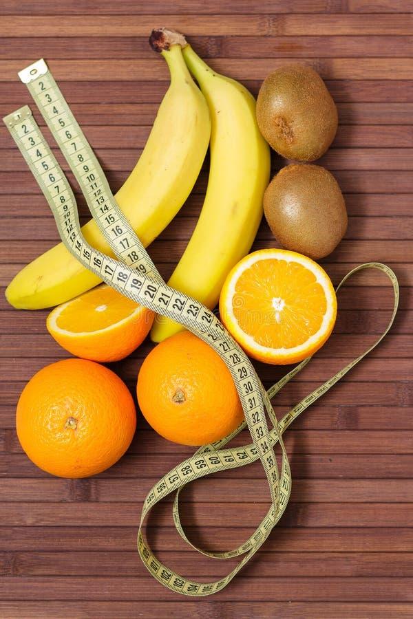 Fruits frais banane, kiwi, orange enveloppée en centimètre, d'isolement sur le fond en bois Nourriture saine Motivation de forme  image libre de droits