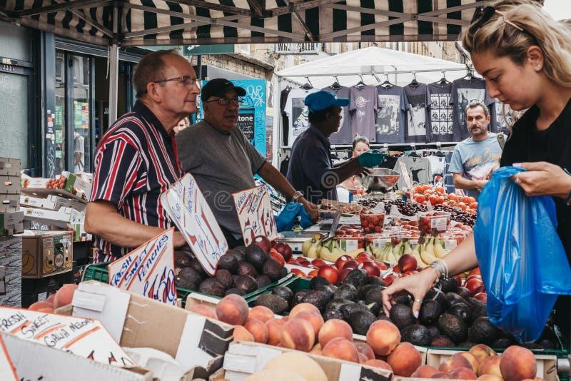 Fruits frais d'achats de femme dans la ruelle de brique, Londres, R-U photo libre de droits