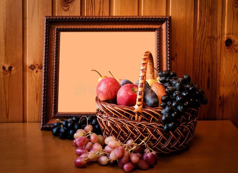 Fruits frais dans le panier et le cadre de tableau Foyer sélectif photographie stock