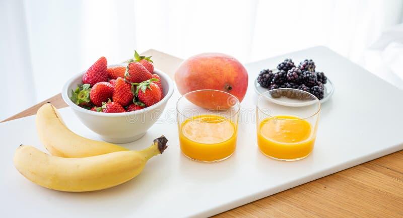 Fruits frais et jus d'orange d'isolement sur le blanc Petit d?jeuner sain pour deux images stock