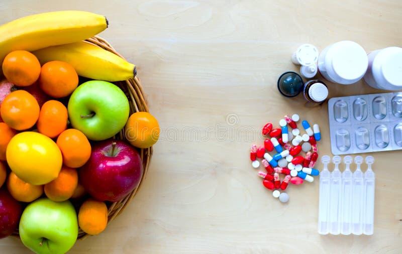 Fruits frais et pilules colorés Concept sain de style de vie image stock