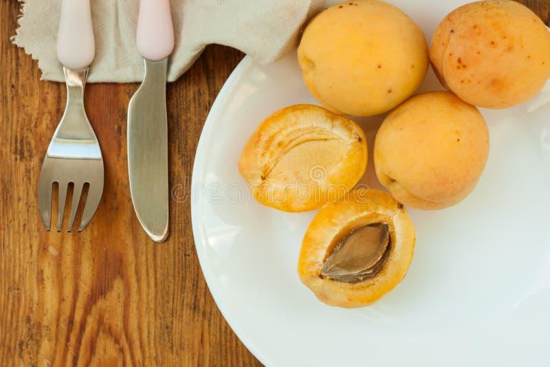 Fruits frais mûrs d'abricot d'un plat blanc sur le fond en bois L'espace de copie, nourriture saine delisious photo stock